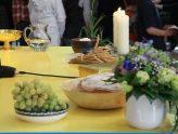 seitlich gesehen festlich gedeckter Altar mit Blumen, Kerzen, Korn und Weintrauben