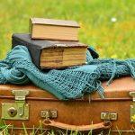 zwei alte Bücher liegen auf einem Koffer wie auf einem Flohmarkt