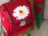 ein roter Schulranzen mit großer Blüte darauf