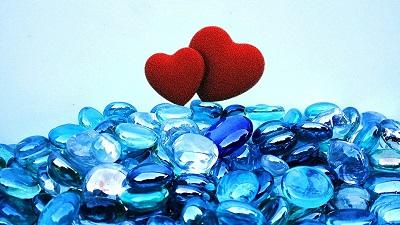 zwei Herzen stehen sich festhaltend auf leuchtend blauen Glassteinen