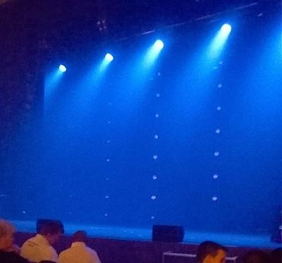 ein blau wirkender Hintergrund, angestrahlt von vier Scheinwerfern