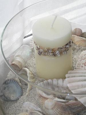 eine Glaschale mit Sand, Muscheln und einer hellen Kerze