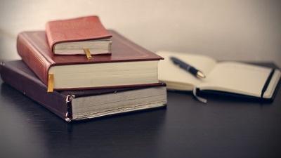 drei Bücher liegen übereinander, ein aufgeschlagender Kalender mit Stift befinden sich im Hintergrund