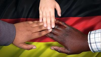 drei Hände aus verschiedenen Nationen berühren sich an den Fingerspitzen, darunter liegt eine Deutschlandfahne