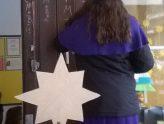 ein Sternsinger schreibt den Segen an, davor steht ein Kind mit Stern in der Hand