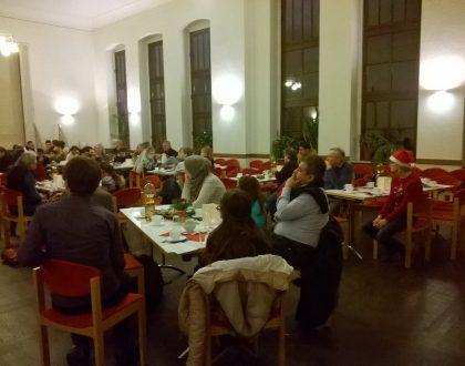 lauschende Menschen sitzen an Tischen in einem großen Saal