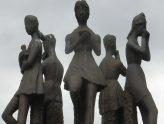 5 Figuren aus Bronze stehen im Kreis mit Blick nach außen