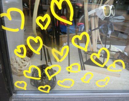 ein mit gelben Herzen beklebtes Schaufenster eines Optikers