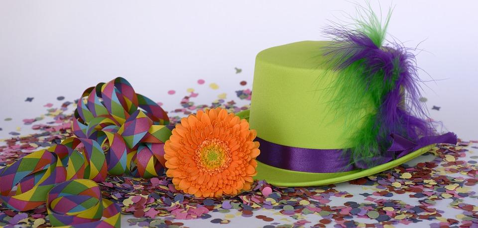 Luftschlange, Blüte und Hut auf Konfetti