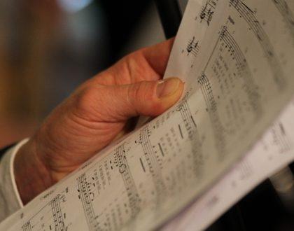 eine Hand hält ein Notenblatt