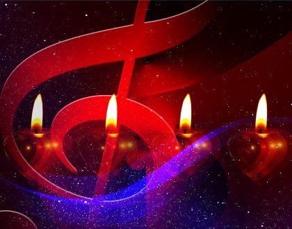 vier Kerzen schimmern hinter einem überdimensionalen Notenschlüssel