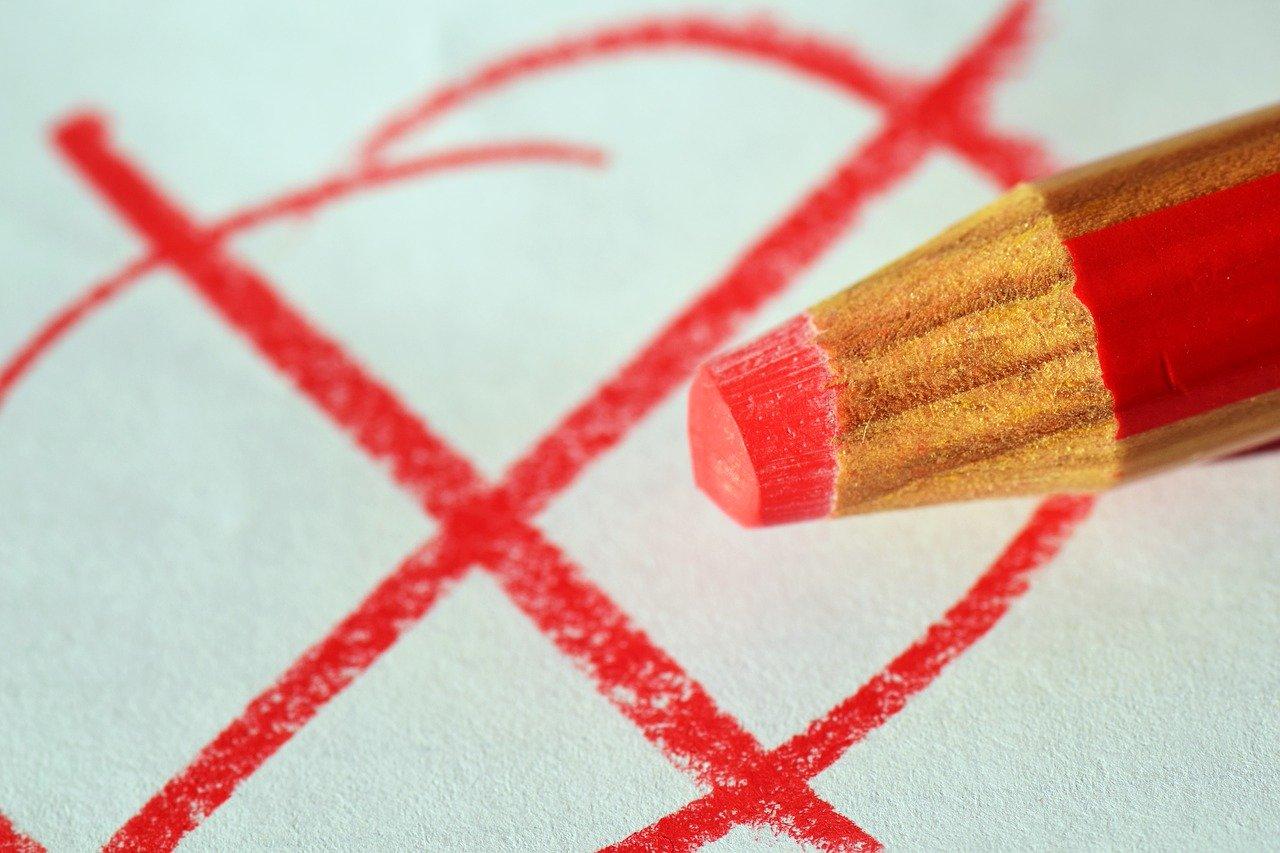 eine Stiftspitze schreibt ein Kreuz zur Wahl