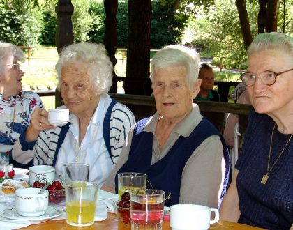 vier Seniorinnen beim Kaffeekränzchen im Freien